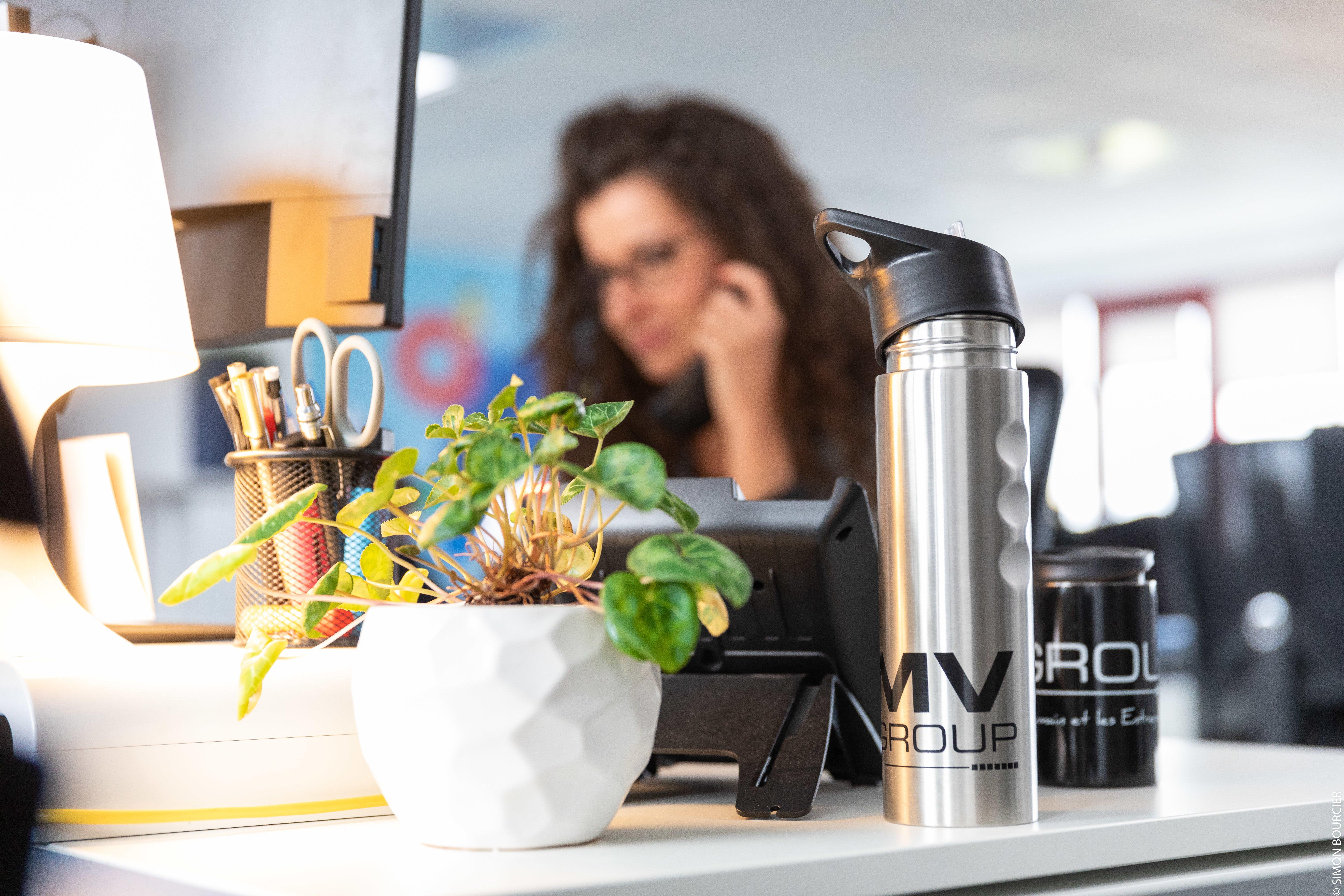 Premier plan : plante en pot et deux mugs MV Group - Second plan : collaboratrice MV Group au téléphone