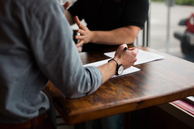 Plan rapproché de deux personnes discutant autour d'un bureau - Photo nik-macmillan