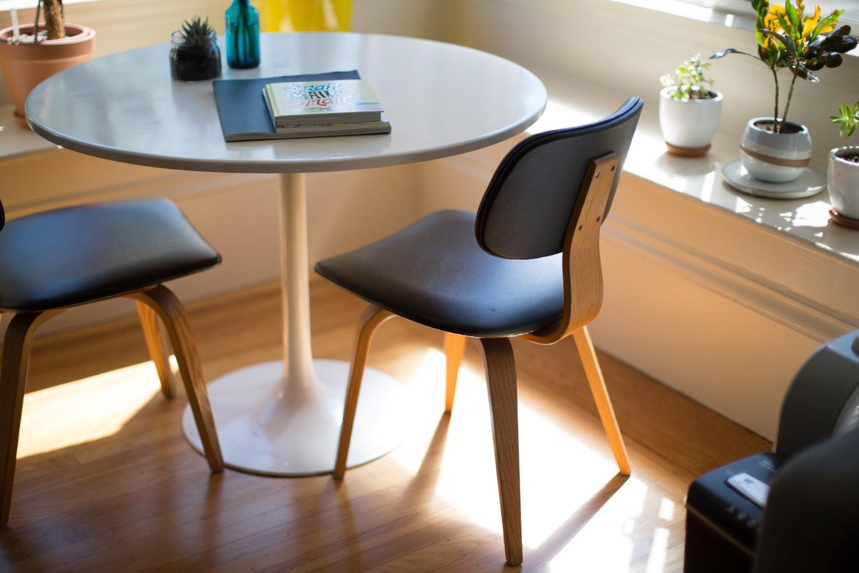 Deux chaises autour d'une table ronde, livres posés sur la table et plantes sur le côté