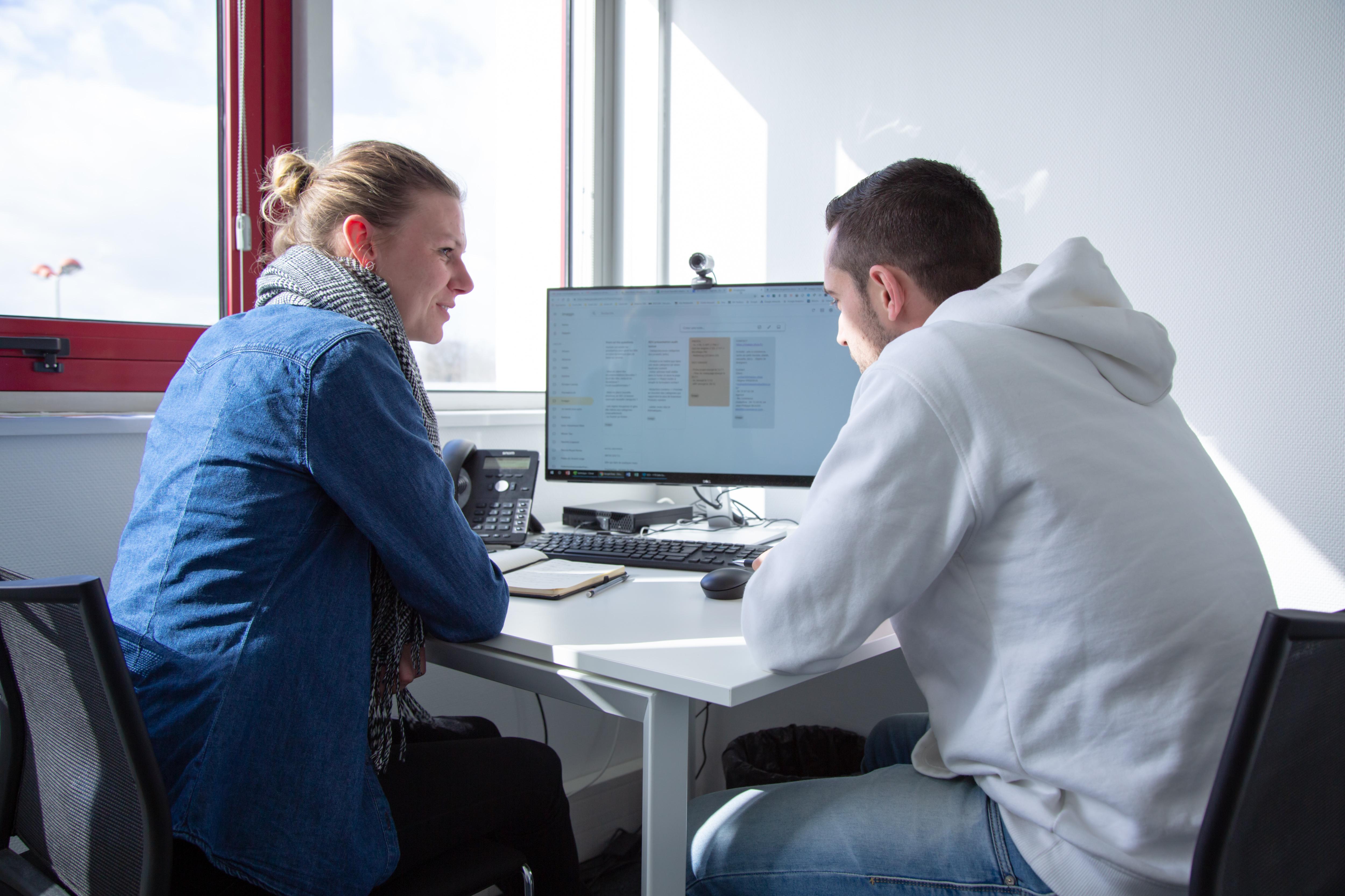 Deux collaborateurs de notre agence digitale de Rennes en réunion face à un ordinateur présentant un planning