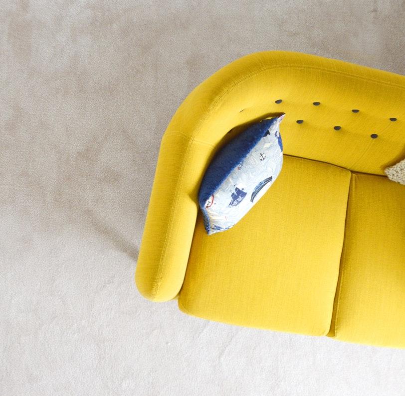 Canapé jaune vu d'en haut avec coussin bleu à motif