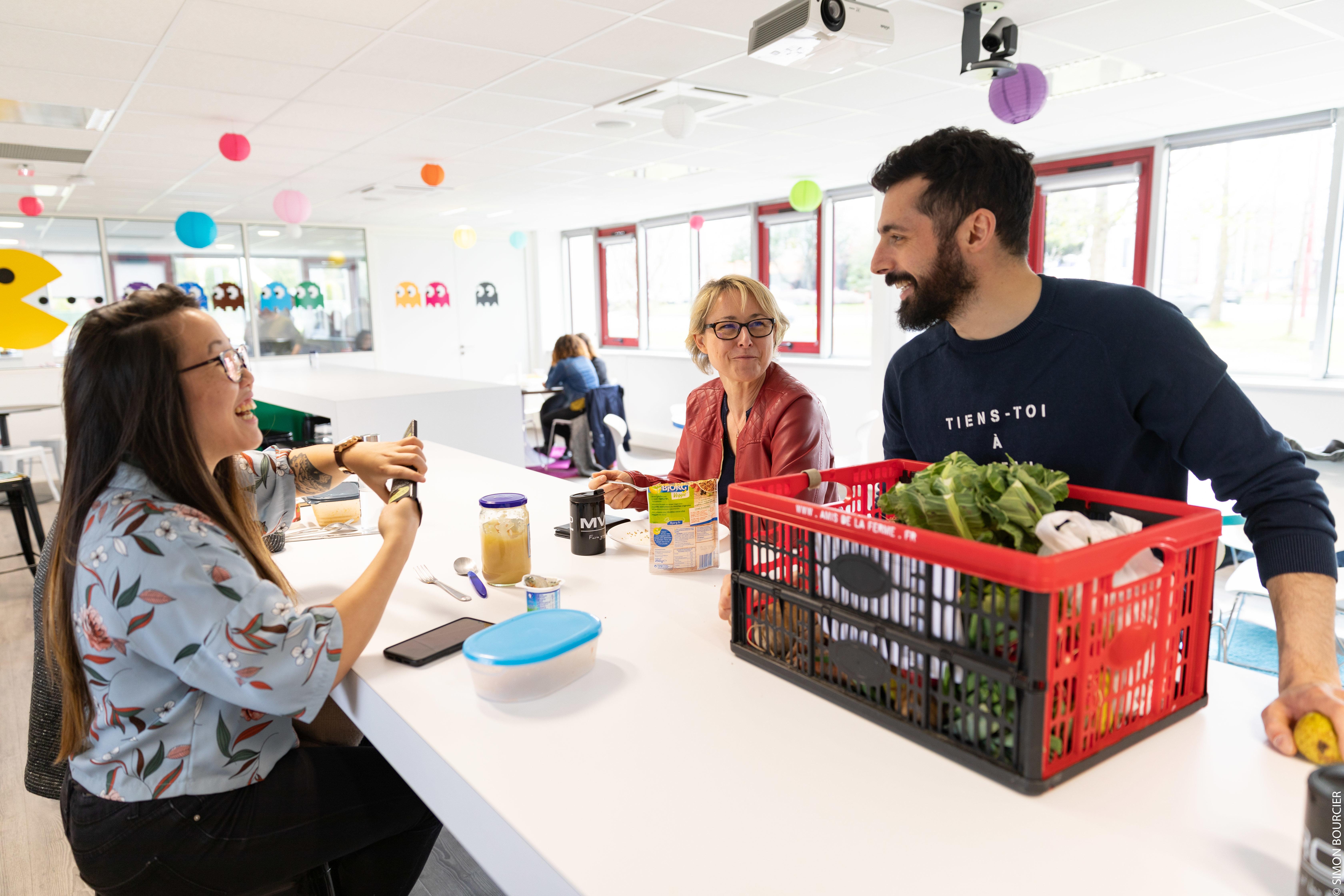 Alexis, Happiness Manager, avec deux collaboratrices devant un panier de légumes dans la cafétéria de MV Group