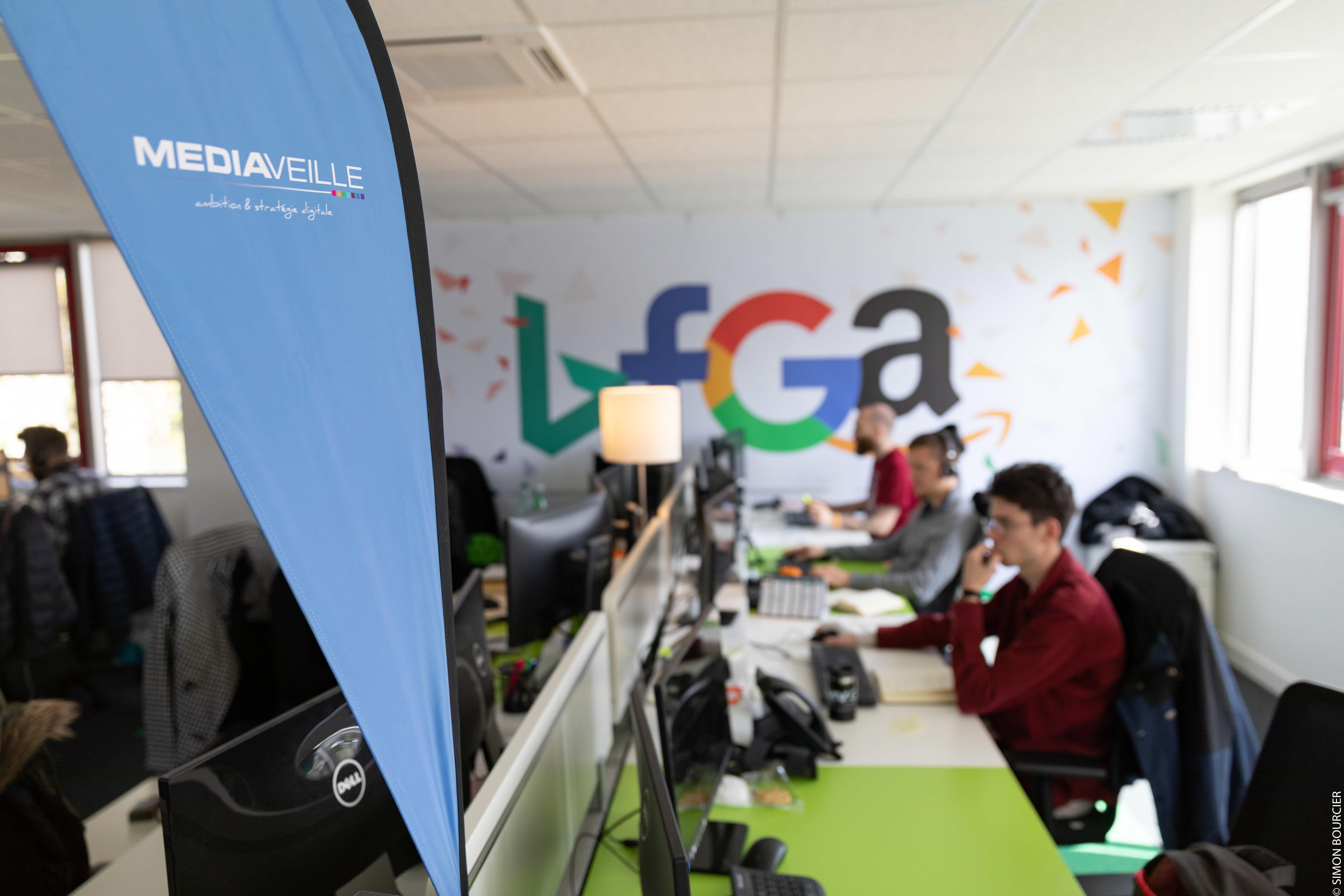 Collaborateurs Mediaveille à leur bureau, avec drapeau bleu et logo Mediaveille au premier plan