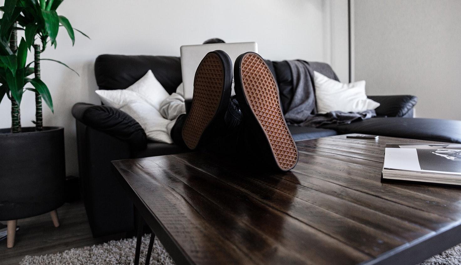 Personne assise sur un canapé, les pieds sur la table basse, avec un ordinateur sur les genoux